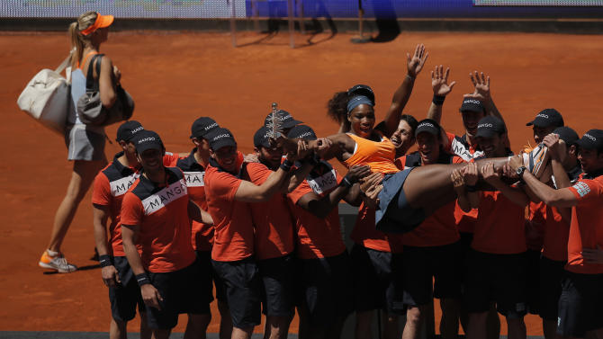 Serena Williams from the U.S., right, poses with her trophy as Maria Sharapova from Russia leaves the court during the women's final match at the Madrid Open tennis tournament, in Madrid, Sunday, May 12, 2013. (AP Photo/Andres Kudacki)