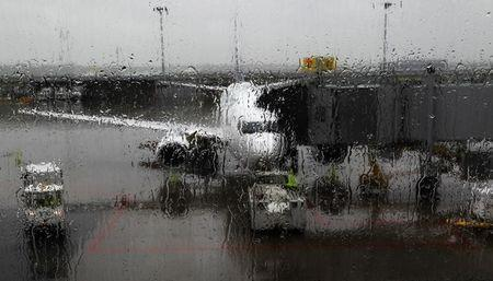 A Westjet aircraft is seen through a rain covered window at Trudeau airport in Montreal