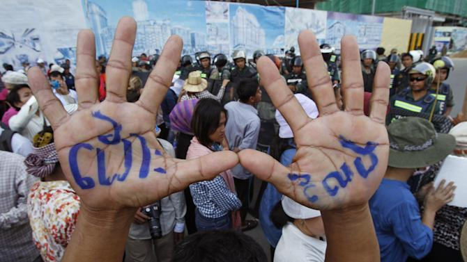"A supporter raises his hands with local letters reading ""Release"" as the others gather at a blocked main street near Phnom Penh Municipality Court in Phnom Penh, Cambodia, Wednesday, July 16, 2014. Five of lawmakers from the main opposition party of Cambodia National Rescue Party appeared in the court Wednesday for being questioned for leading about a hundred of their supporters Tuesday to demonstrate in front of the park, asking authorities to open the site to the public. (AP Photo/Heng Sinith)"