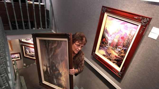 """FILE - In this April 9, 2012 file photo, Denice Gould, an employee of the Thomas Kinkade Gallery carries one of the artist's works up a flight of stairs in Placerville, Calif. Kinkade, 54, the self-described """"Painter of Light,"""" died April 6 at his home in Los Gatos, Calif. (AP Photo/Rich Pedroncelli, file)"""