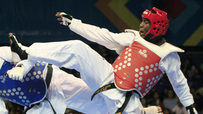 FILE - In this Oct. 18, 2011 file photo, Jamaica's Kenneth Edwards fights Canada's Francois Coulombe during a quarterfinal men's taekwondo +80 kg match at the Pan American Games in Guadalajara, Mexico. Edwards said on Tuesday, Oct. 15, 2013 he has tested positive for a banned substance and will challenge the findings. His announcement comes as the world's anti-doping authority launches a sweeping audit of Jamaica's drug-testing agency amid allegations of inconsistent testing. (AP Photo/Martin Mejia, File)