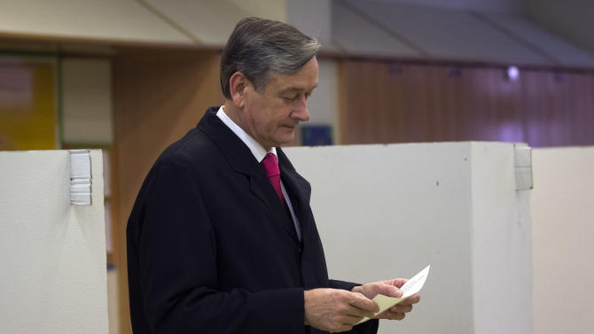 Slovenian President Danilo Turk holds his ballot to cast it at a polling station in Ljubljana, Slovenia, Sunday, Nov. 11, 2012. Three candidates, including Turk, are vying for the presidency in Slovenia, a tiny, economically troubled European Union nation that is riven by deep political divisions and is in danger of needing a bailout. (AP Photo/Darko Bandic)