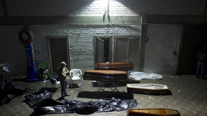A man stands around coffins containing the remains of victims after the bodies were identified at a gymnasium in Santa Maria city, Rio Grande do Sul state, Brazil, Sunday, Jan. 27, 2013. A fast-moving fire roared through the crowded, windowless Kiss nightclub in southern Brazil early Sunday, within seconds filling the space with flames and a thick, toxic smoke that killed more than 230 panicked partygoers who gasped for breath and fought in a stampede to escape.(AP Photo/Felipe Dana)