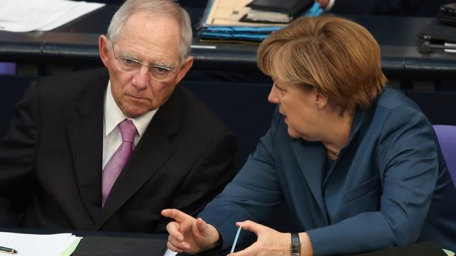 German Chancellor Angela Merkel and Finance Minister Wolfgang Schauble discuss E.U. financial aid to Cyprus on April 18.