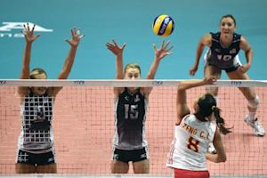 Kimberly Hill of the USA (C) attempts to block a spiked…