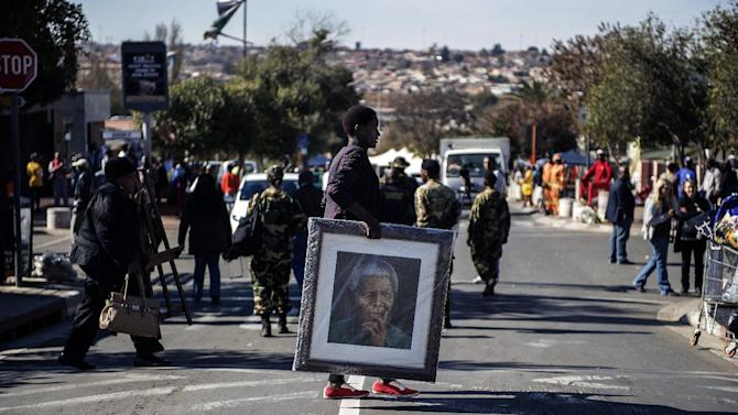 A woman carries a painting of late Nelson Mandela outisde his former house in Soweto on July 18, 2014