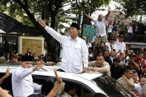 Indonesian presidential candidate Subianto and his vice presidential running mate Rajasa wave to supporters after registering their bid for the upcoming July 9 election in Jakarta