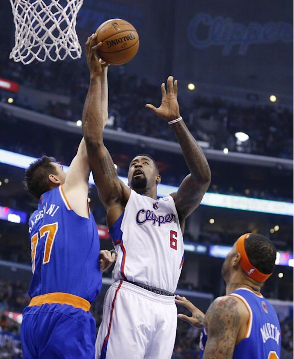 Los Angeles Clippers' DeAndre Jordan, center, shoots over New York Knicks' Andrea Bargnani, of Italy, left, and Carmelo Anthony, right, during the first half of an NBA basketball game in Los Angeles,