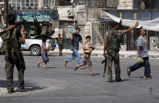 Civilians run past a Free Syrian Army checkpoint in the Saif al-Dawla neighbourhood of the northern Syrian city of Aleppo on August 14