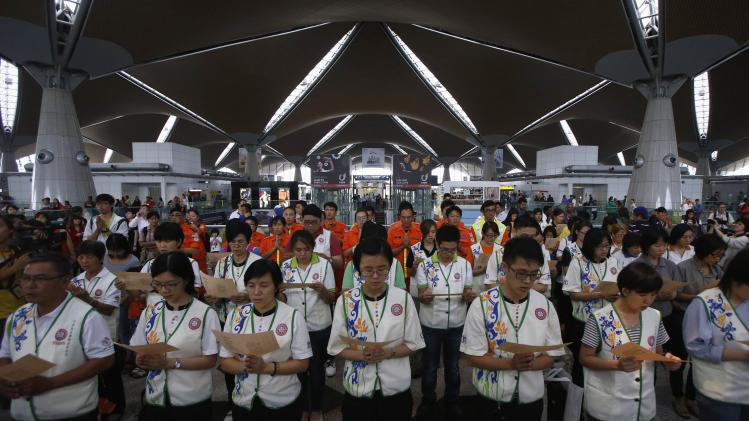 Volunteer rescue workers and religious organizations pray during multi-religion mass prayers for the passengers of Malaysian Airlines flight MH370, at Kuala Lumpur International Airport in Sepang
