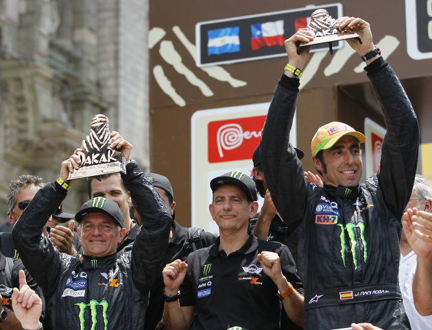 "Mini driver Joan ""Nani"" Roma, of Spain, right, and co-driver Michel Perin, from France, hold up their second place trophies at the 2012 Argentina-Chile-Peru Dakar Rally podium ceremony in Lima, Peru,"