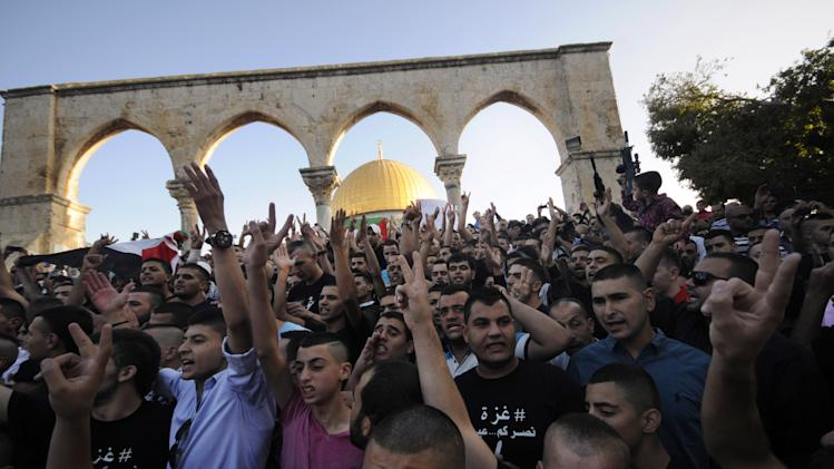 Muslim worshippers chant slogans during a protest against the fighting in Gaza following a prayer during the first day of Eid al-Fitr, which marks the end of the Muslim fasting month of Ramadan, at the Al Aqsa Mosque compound in Jerusalem's Old City, Monday, July 28, 2014. (AP Photo/Mahmoud Illean)