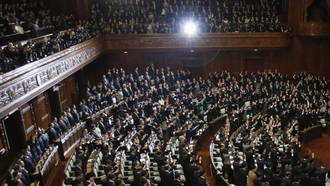 """Lower House lawmakers raise their hands and shouts """"banzai"""" (cheers) after the dissolution of lower house was announced at the Parliament in Tokyo"""