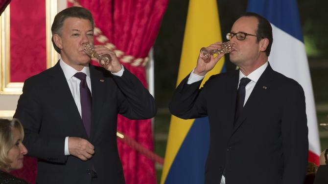 French President Hollande toasts with Colombian President Juan Manuel Santos during an official dinner at the Elysee Palace in Paris