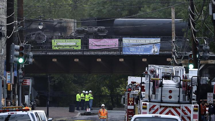 Officials stand underneath a bridge where part of a CSX freight train derailed overnight in Ellicott City, Md., Tuesday, Aug. 21, 2012. Authorities said two people not employed by the railroad were killed in the incident. (AP Photo/Patrick Semansky)