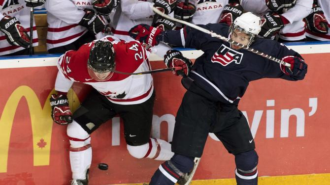 Canada forward Mark McNeill, left, hits Team USA forward Ryan Hartman, right, during first period semi-final IIHF World Junior Championships hockey action in Ufa, Russia on Thursday, Jan. 3, 2013. (AP Photo/The Canadian Press, Nathan Denette)