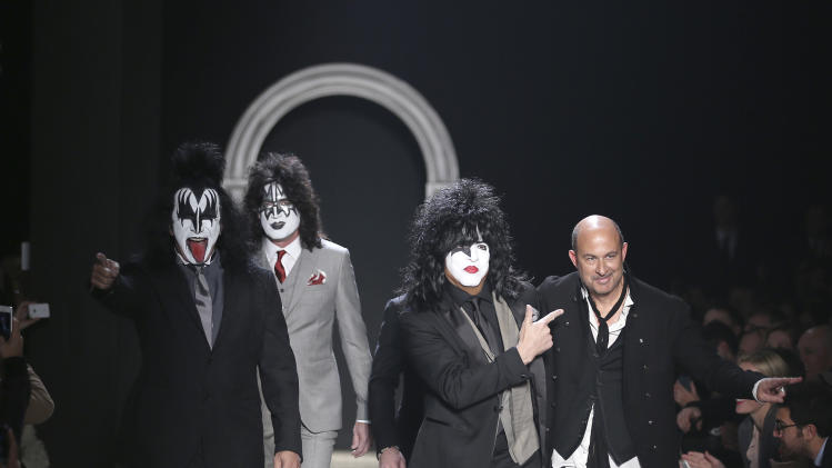 American fashion designer John Varvatos, right, is accompanied by Rock Band Kiss as he acknowledges the applause of the audience, at the end of his men's Autumn-Winter 2014 collection, part of the Milan Fashion Week, unveiled in Milan, Italy, Saturday, Jan. 11, 2014. (AP Photo/Antonio Calanni)