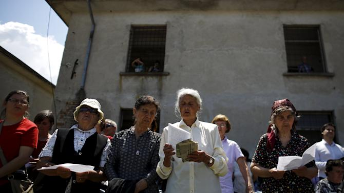 Women read a prayer during a religious mass outside the crumbling building of a communist-era prison built on the site of former labour camp Belene in Persin
