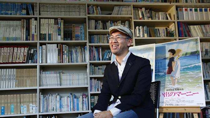 "In this Feb. 1, 2016 photo, Japanese director Hiromasa Yonebayashi smiles about his latest film ""When Marnie Was There"" with its poster during an interview at his office, Studio Ghibli, in suburban Tokyo. The coming-of-age story is familiar: A shy girl has problems fitting in and concocts an imaginary friend. The originality of the Oscar-nominated ""When Marnie Was There"" comes from how its hand-drawn images express the girl's inner torment. Luscious hand-drawn animation is the trademark of Japan's renowned Studio Ghibli, where the film's director Yonebayashi worked for years. (AP Photo/Shizuo Kambayashi)"