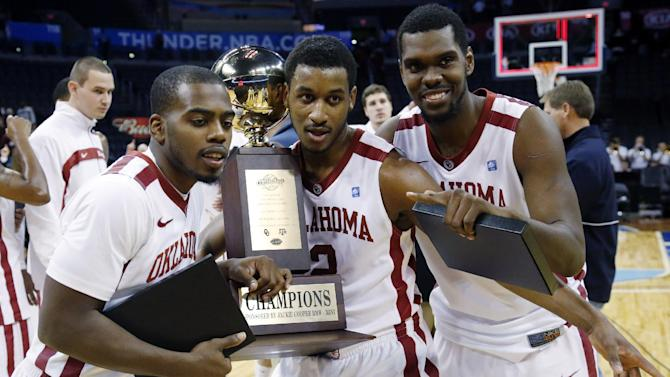 Oklahoma guards Sam Grooms, from left, Steven Pledger, and forward Andrew Fitzgerald pose with the  trophy after defeating Texas A&M 64-54 in an NCAA college basketball game in the All College Classic tournament in Oklahoma City, Saturday, Dec. 15, 2012. (AP Photo/Sue Ogrocki)