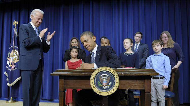 President Barack Obama, accompanied by Vice President Joe Biden and children who wrote the president about gun violence following last month's shooting at an elementary school in Newtown, Conn., signs executive orders, Wednesday, Jan. 16, 2013, in the South Court Auditorium at the White House in Washington. The children and their parents from left, Hinna Zeejah, 8, and Nadia Zeejah, Hinna's mother, Taejah Goode, 10, and Kimberly Graves, Taejahís mother, Julia Stokes, 11, and Dr. Theophil Stokes, Julia's father, and Grant Fritz, 8, and Elisabeth Carlin, Grant's mother. (AP Photo/Susan Walsh)
