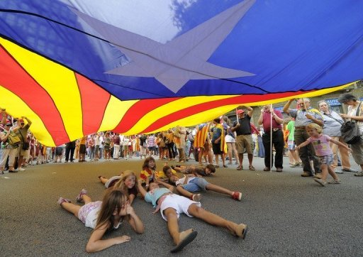 Children gather under a giant Catalan flag in Barcelona in 2011