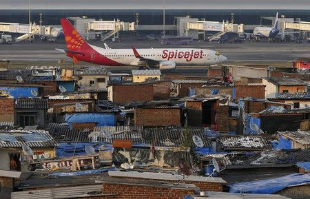 A SpiceJet passenger aircraft taxis on the runway at the airport next to a slum area in Mumbai