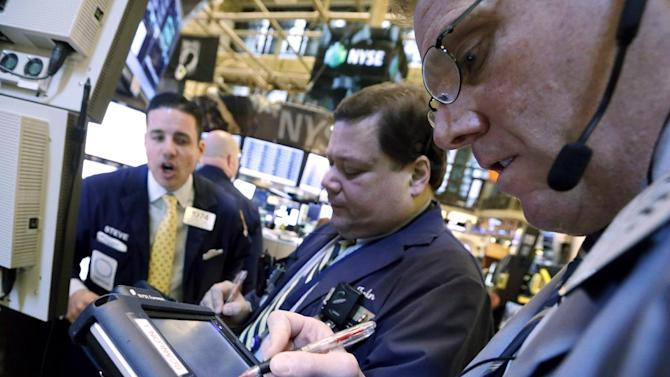 In this Thursday, Jan. 10, 2013, photo, traders work on the floor of the New York Stock Exchange. Stocks opened lower on Wall Street on Tuesday, Jan. 15, 2013,  as concerns about the government's finances intensified, offsetting a report that showed retail sales rose in December.  (AP Photo/Richard Drew)