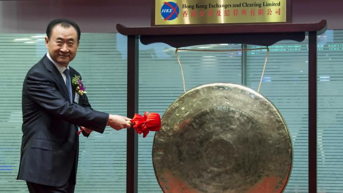 Wang Jianlin, chairman of Wanda commercial properties, strikes a gong during the debut of the company at the Hong Kong Stock Exchange