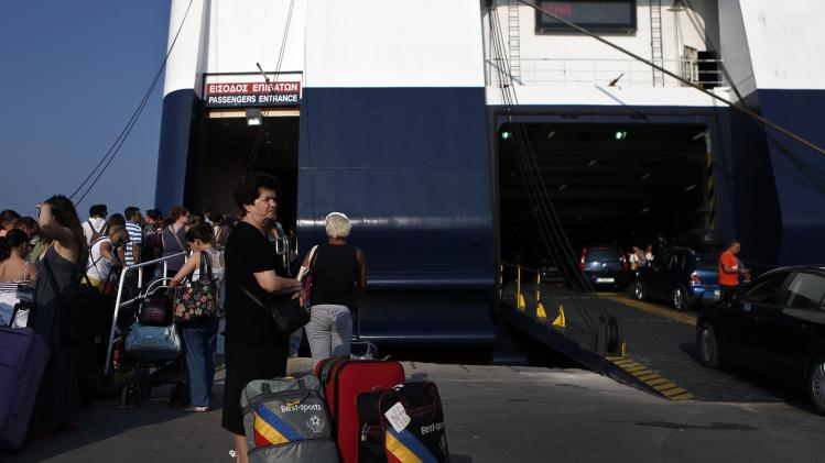 Passengers wait to board a ship at the port of Piraeus
