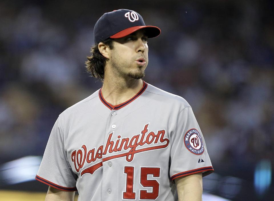 Washington Nationals pitcher Dan Haren looks at the scoreboard as he returns to the dugout after retiring the Los Angeles Dodgers in the second inning of a baseball game in Los Angeles Tuesday, May 14, 2013. (AP Photo/Reed Saxon)
