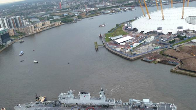 In this photo issued by Britain's Ministry of Defence, showing 150 sailors and aircrew recreating the Olympic Rings on the flight deck of HMS Ocean, to mark the start of the ship's Olympic deployment as it arrives Friday July 13, 2012 at Greenwich on the River Thames in London, where she will be acting as a helicopter landing platform and logistics hub.  The 21,500 ton helicopter carrier will also be home for 400 military personnel providing security in Greenwich Park, where the equestrian events and modern pentathlon will take place. The O2 arena, dome at top right, which is being renamed as the North Greenwich Arena during the Olympic Games. (AP Photo/MoD) NO SALES