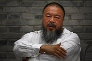 Chinese dissident artist Ai Weiwei folds his arms as he sits on a chair in the courtyard of his studio in Beijing June 20, 2012. REUTERS/David Gray