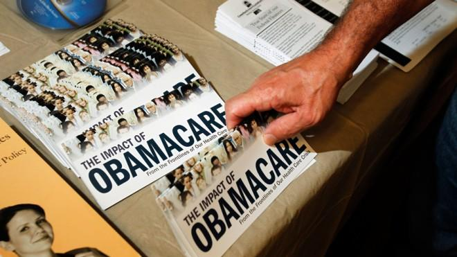 A Tea Party member reaches for a pamphlet on the impact of ObamaCare.