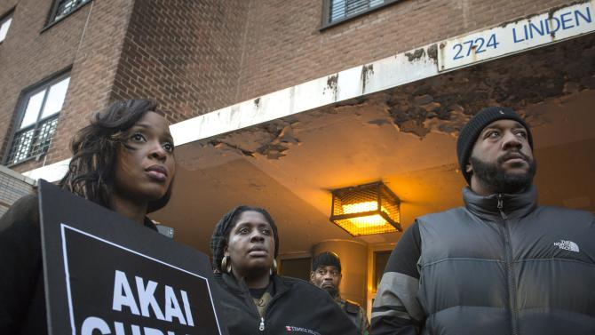 A woman, demanding justice for Akai Gurley, holds a placard at the site of his shooting death in Brooklyn