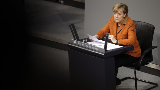 German Chancellor Angela Merkel speaks during a government statement as part of a meeting of the German federal parliament, Bundestag, in Berlin, Germany, Wednesday, Jan. 29, 2014. Due to a hip injury Merkel has to sit during her speech. The reflections are caused by windows at the visitors tribune. (AP Photo/Michael Sohn)