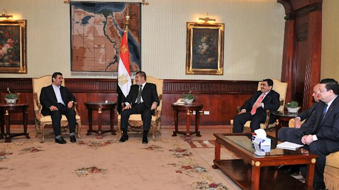 In this image released by the Egyptian Presidency, Iran's President Mahmoud Ahmadinejad, left, and Egyptian President Mohammed Morsi, center, meet in Cairo, Egypt, Tuesday, Feb. 5, 2013. Ahmadinejad arrived in Cairo on Tuesday for the first visit by an Iranian leader in more than three decades, marking a historic departure from years of frigid ties between the two regional heavyweights.(AP Photo/Egyptian Presidency)