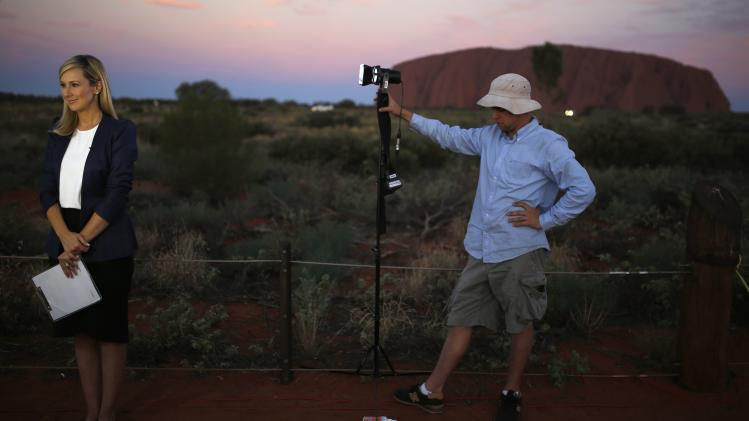A television reporter prepares to broadcast from a media position at Uluru