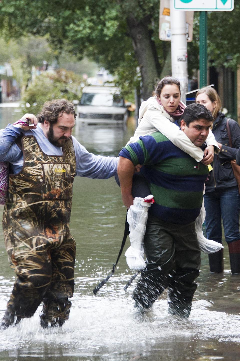 A resident is carried through floodwaters in Hoboken, N.J. on Tuesday, Oct. 30, 2012 after superstorm Sandy made landfall in New Jersey Monday evening. (AP Photo/Charles Sykes)