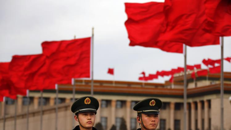 Red flags flutter as paramilitary policemen stand guard on the Tiananmen Square near the Great Hall of the People during the closing ceremony of the CPPCC, in Beijing