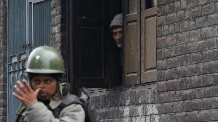 A Kashmiri civilian watches from the window of his house as an Indian paramilitary soldier stands guard during restrictions in Srinagar, India, Sunday, March 16, 2014 Kashmiri separatists called for a strike Sunday to protest the killing of a teenager boy by government forces in the troubled Indian portion of Kashmir. (AP Photo/Mukhtar Khan)