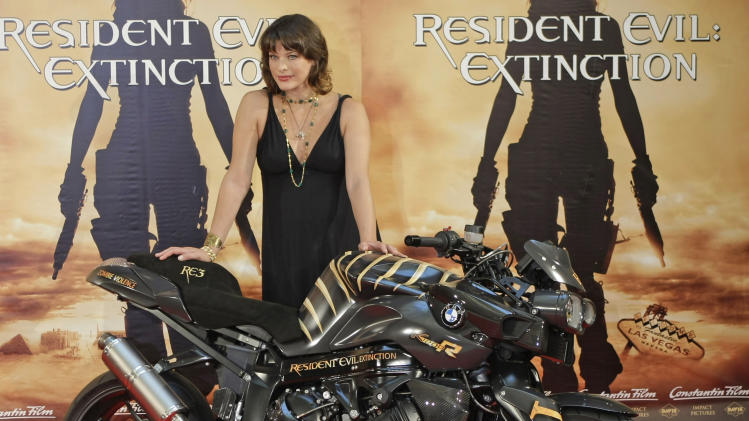 "FILE - In this Mon., July 16, 2006 file photo, actress Milla Jovovich poses behind a motorcycle, during a photocall for the latest ""Resident Evil"" movie in Munich, southern Germany. Born in Kiev, she was spotted at age 11 by famed photographer Richard Avedon, who featured her in Revlon's ""Most Unforgettable Women in the World"" ads. Jovovich went on to appear on dozens of magazine covers and in campaigns for several brands including Banana Republic, Donna Karan, Gap and Versace. But she's also carved out a major acting career as star of the sci-fi ""Resident Evil"" series (directed by her husband, Paul W.S. Anderson) and has appeared in films as varied as ""The Fifth Element"" ""He Got Game"" and ""Stone."" (AP Photo/Uwe Lein, File)"