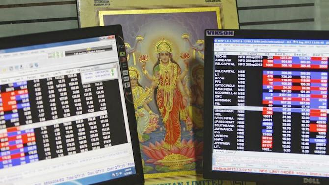 An image of Lakshmi, is placed between monitors displaying share price index at a share trading market in the northern Indian city of Chandigarh