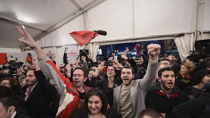 Syriza supporters celebrate after the first exit polls