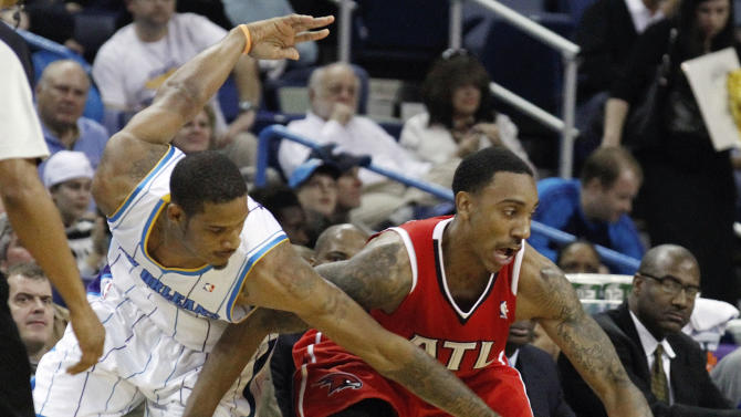 New Orleans Hornets small forward Trevor Ariza, left, reaches in on Atlanta Hawks guard Jeff Teague in the first half of an NBA basketball game in New Orleans,  Sunday, Jan. 29, 2012.    (AP Photo/Bill Haber)