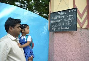 A man holds his daughter as they look at a noticeboard …