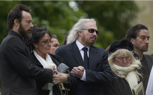 Barry Gibb, center, and Robin Gibb's wife Dwina Gibb, right, who holds an order of service, react at the graveside during the burial of Robin Gibb outside St Mary's Church in Thame, England, Friday, J