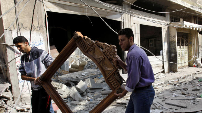 Palestinians carry a frame from the destroyed house of Islamic Jihad militant Hasam Al Kholy, hit overnight in an Israeli strike on Gaza City, Tuesday, Nov. 20, 2012. Efforts to end a week-old convulsion of Israeli-Palestinian violence drew in the world's top diplomats on Tuesday, with President Barack Obama dispatching his secretary of state to the region on an emergency mission and the U.N. chief appealing from Cairo for an immediate cease-fire.(AP Photo/Adel Hana)