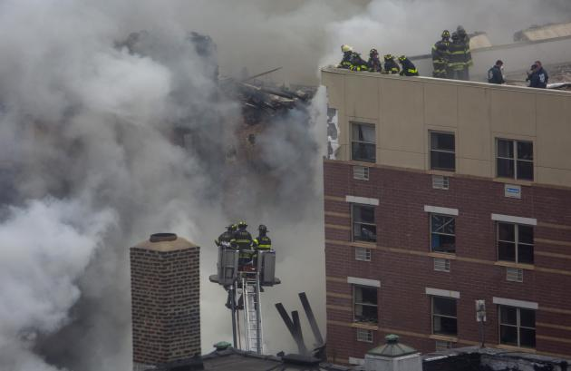 New York City firefighters examine the rubble at an apparent building explosion fire and collapse in the Harlem section of New York