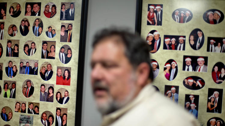 In this Jan. 15, 2013, photo, photos of workers with their families hang on the wall in the break room of Factory Automation Systems as Rosser Pryor, co-owner and President, right, looks on at the company's Atlanta facility. Pryor, who cut 40 of 100 workers since the recession, says while the company is making more money now and could hire ten people, it is holding back in favor of investing in automation and software. (AP Photo/David Goldman)